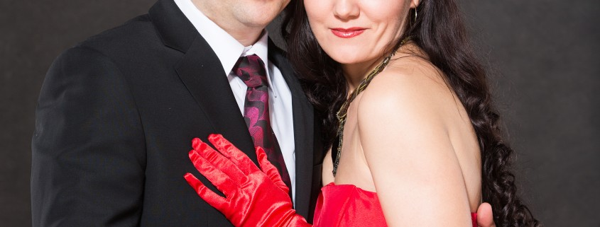 Portrait of happy couple in love posing at studio on gray background dressed in red. Attractive man and woman.